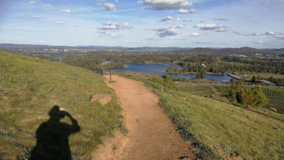 Path along the contour, Dairy Farmer Hill, with Lake Burley Griffin behind. National Arboretum, Canberra.