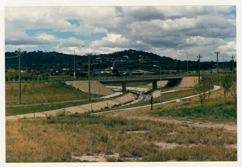 Isabella Drive looking east from Ashley Drive. Pathways along both sides of stormwater drain, underpassing Isabella Drive. c1989