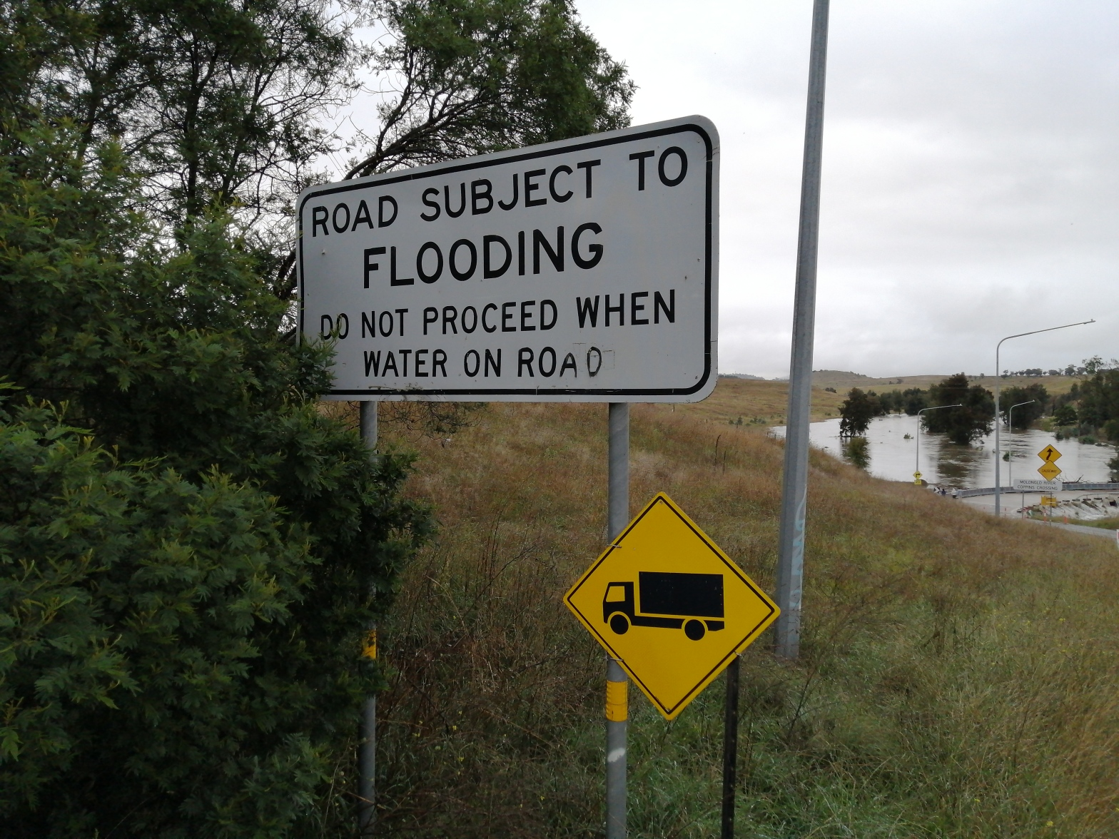 """""""Road subjected to flooding"""" sign. Flood water, Coppins Crossing, Molonglo River, Molonglo Valley, 24 March 2021"""